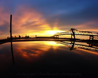 The River Runs, Mississippi River and reflections of the Horace Wilkinson Bridge of Baton Rouge, Louisiana during a dramatic sunset