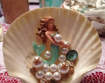Darling hanging clam shells with mermaids in bubbles.