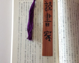 Bookworm in Japanese calligraphy on a wooden bookmark with a purple tassel