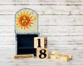 Whimsical perpetual wooden calendar with day cubes and months in a caddy box