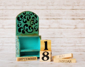 Wooden perpetual calendar in vintage style with day cubes and months in a caddy box