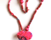 Long beaded necklace with red, hot pink and purple beads with handmade pom poms Valentine's Day An Astrid Endeavor statement necklace