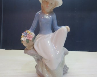 Blue And White Girl Figurine Resting With Basket Of Flowers