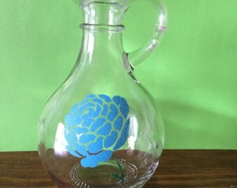 Glass pitcher, blue flower stenciled on it, can be used as vase or cruet