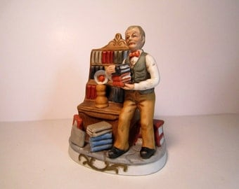 Man Holding Books Figurine Next to a Bookcase. (#187)