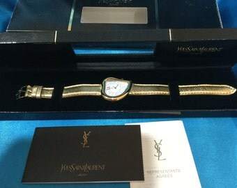 Authentic Yves Saint Laurent  1990's heart face YSL  gold tone watch gold leather band. Genuine Brand NEW in Box, serial no 42024
