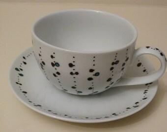 Unique hand painted porcelain tea cup and saucer.
