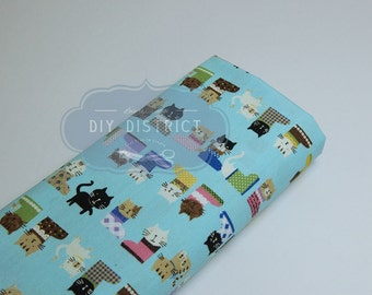 Fabric cats in boots light blue background.