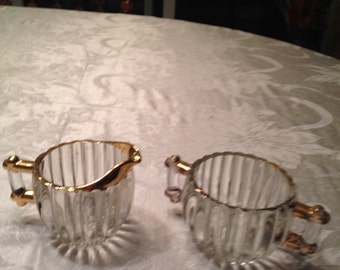 Beautiful vintage glass cream and sugar outlined in a gold color