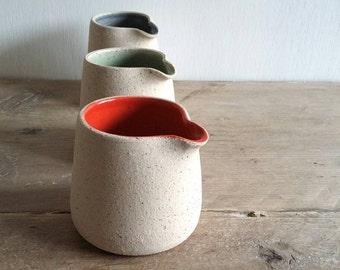 Colourful cream jugs