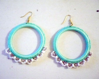 Hoop mint crochet earrings with white and translucent glass beads.