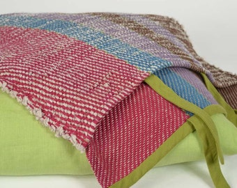 Handwoven cushion of linen. Bright colours: green, raspberry, blue, mauve and brown. Pillow with two covers, apple green and multicoloured.