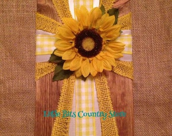 Yellow sunflower with checks wooden cross.