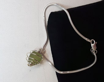 "Beautiful green sea glass wrapped in a silver cage on a 7"" sterling silver snake chain bracelet."