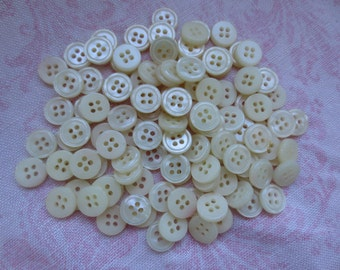 Vintage beautiful cream color pearlized round plastic buttons. Lot of 110 buttons.