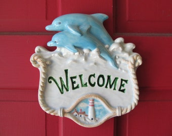 Dolphin and lighthouse welcome sign