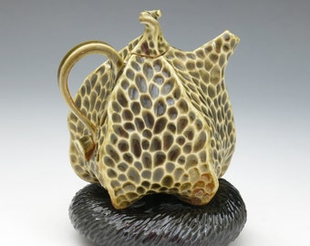 Carved porcelain pod teapot in olive green with black pillow, green celadon
