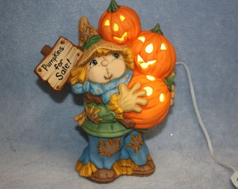 Hand Painted Ceramic Scarecrow holding three lighted Jack O Lanterns with a Pumpkins for Sale sign