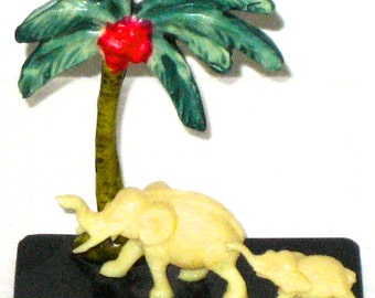 Vintage celluloid elephants with palm tree made in Japan trunk up