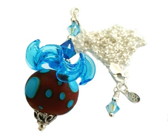 Red and blue lampwork necklace with bright blue ruffled glass bead, topped with blue Swarovski crystals, Sterling silver