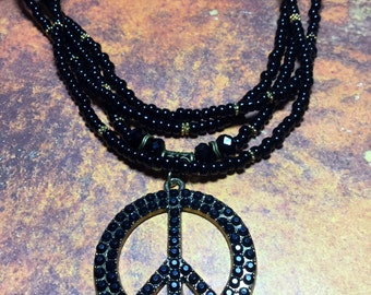 Black rhinestone peace sign pendent, four stranded black and brass beaded Necklace