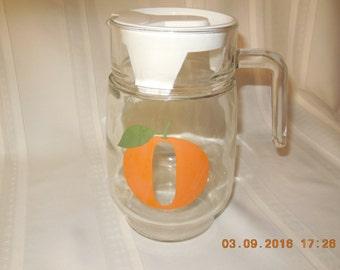 Vintage orange juice juice pitcher with white plastic lid.
