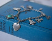 Cute 50's charm bracelet. Silver, with turqoise turtle, horse, tennis, heart, airplane, bicycle, skull, violin