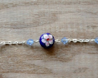 Bracelet. A textured silver plated cable bracelet set with a  round shaped flower designed blue Cloisonne bead, and acrylic bicone beads.