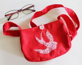 A little red bag with a long shoulder strap and a swallow in Liberty