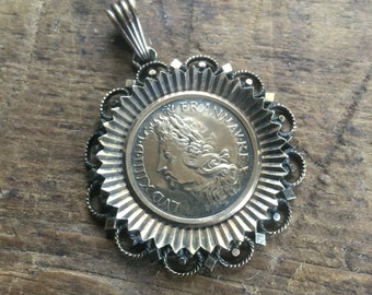 Coin pendant in decorative mount
