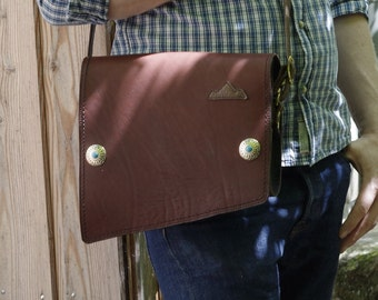 shoulder bag flap decorated with two conchos