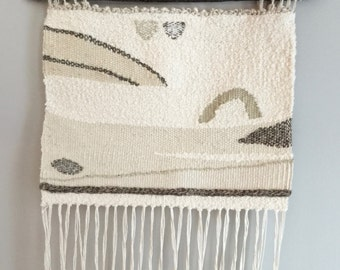 Woven wall hanging neutrals and sea greens hung on branch weaving 100% natural fibres