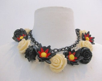 Short necklace using small carved flowers on link chain. Black and white and red colors.  One of a kind, toggle closing.