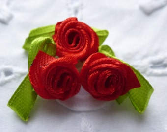 Red satin roses.   Approximately 16mm wide and 25mm across.  Set of 20