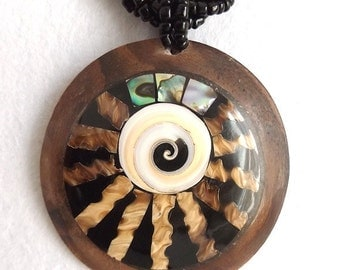 Abalone and white shell round wooden necklace. rays of natural shell with white swirl spiral design. Black twisted bead rope style chain.