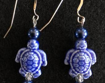 Sterling Silver Wires with Ceramic Turtle and blue glass pearls.