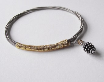 Guitar string bracelet with pinecone charm