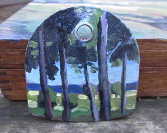 Metal tag with painting of trees and the beach beyond