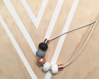 "Polymer clay bead necklace. Marble, copper, grey, black white ""the bella on braided leather"""