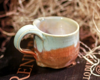 Small wheel-thrown mug with browns and light green glazes and comfortable handle