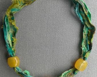 Textile boho necklace. Green in monochrome.