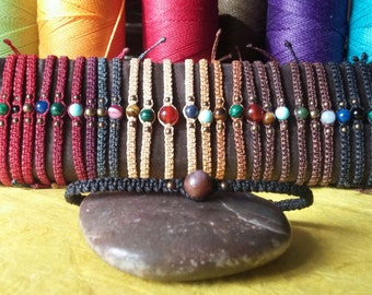 A handmade macrame bracelet with semi-precious stones, brass balls and sliding and adjustable fastening waxed thread.