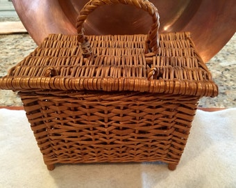 Cute vintage wicker sewing basket with braided handle and lid.