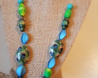 Blue and green necklace with some handmade beads and other contrasting beads and a toggle clasp