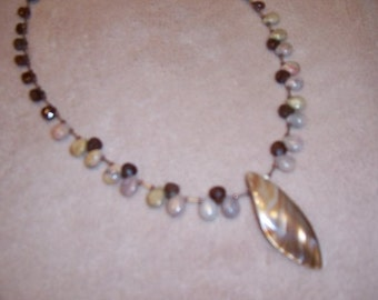 Beaded necklace with shell pendant.