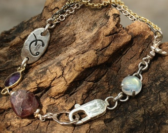 Ruby and moonstone charm bracelet with triple strand silver chain