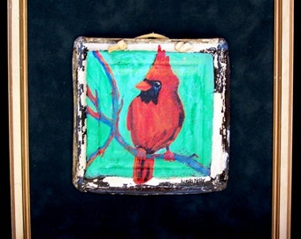 Showy Red Cardinal on antique tin tile,matted on green suede,framed