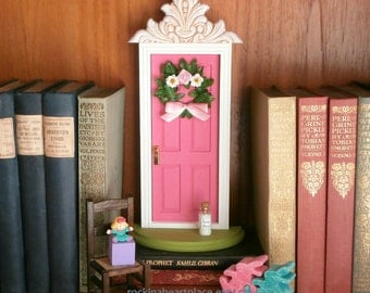 Fairy Door or Tooth Fairy Door, made of wood, in bright pink, with architectural detail and handmade wreath