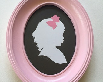 FRAMED Custom Silhouette Portrait: 5x7, White Silhouette, Black Background, with Color Embellishment, in Pink Oval Frame.