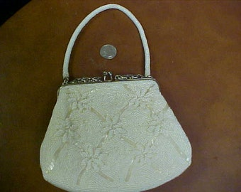 beaded white purse- with flower pattern- has beaded strap- nice